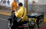 济南:外卖小哥不顾安全 骑车拿手机抢单被罚
