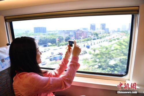 """图为""""复兴号""""高铁旅客拿手机拍摄窗外景色。 <a target='_blank' href='http://www.chinanews.com/'>中新社</a>记者 陈文 摄"""
