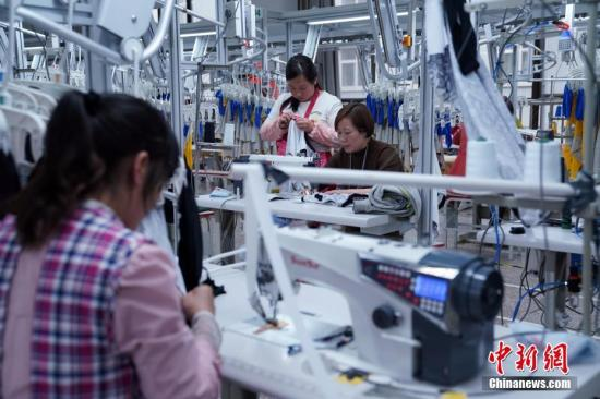 3月31日,工人在勉县制衣厂生产线工作。勉县与政力制衣(厦门)有限公司签订合作协议,成为苏陕扶贫协作和经济合作启动以来首个在勉县落地的项目,目前已经正式建成投产。该项目总投资2000余万元,建成自动化生产流水线15条,主要从事服装制造、销售产业。预计实现年应税销售1.2亿元、税收200万元,吸纳群众就业500余人。 毛建军 摄