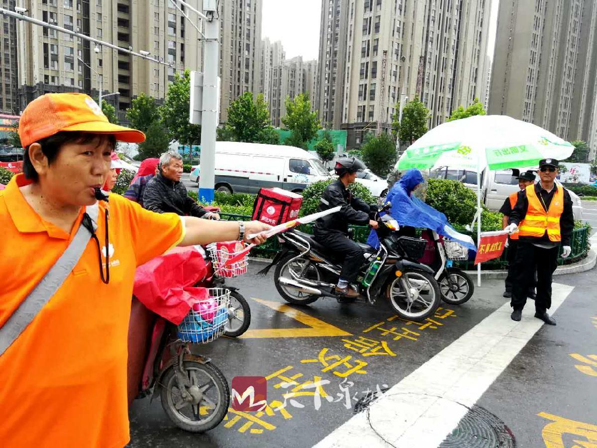 交通文明志愿者在引导市民有序通过路口