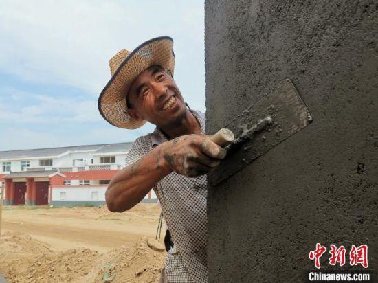 菏泽市鄄城县旧城镇村民在旧城镇实施的滩区改造工程项目打工,建设自己未来的新房。 杨飞 摄